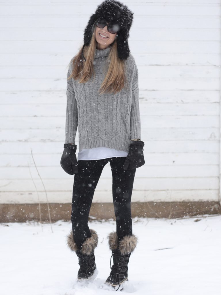 snow day outfit with gray cable knit sweater and Sorel snow boots
