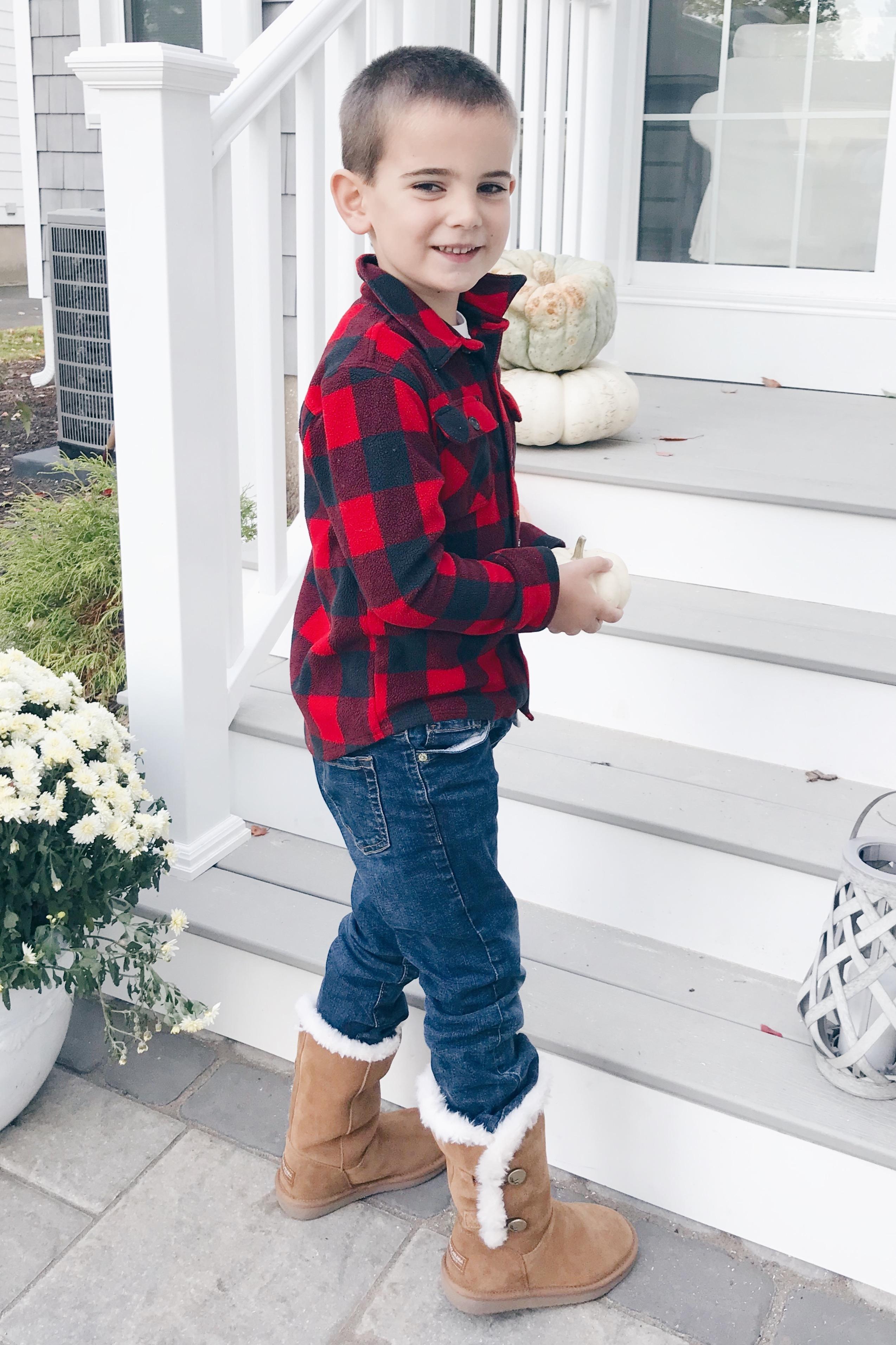 preschool boy decorating fall porch wearing kollaburra boots