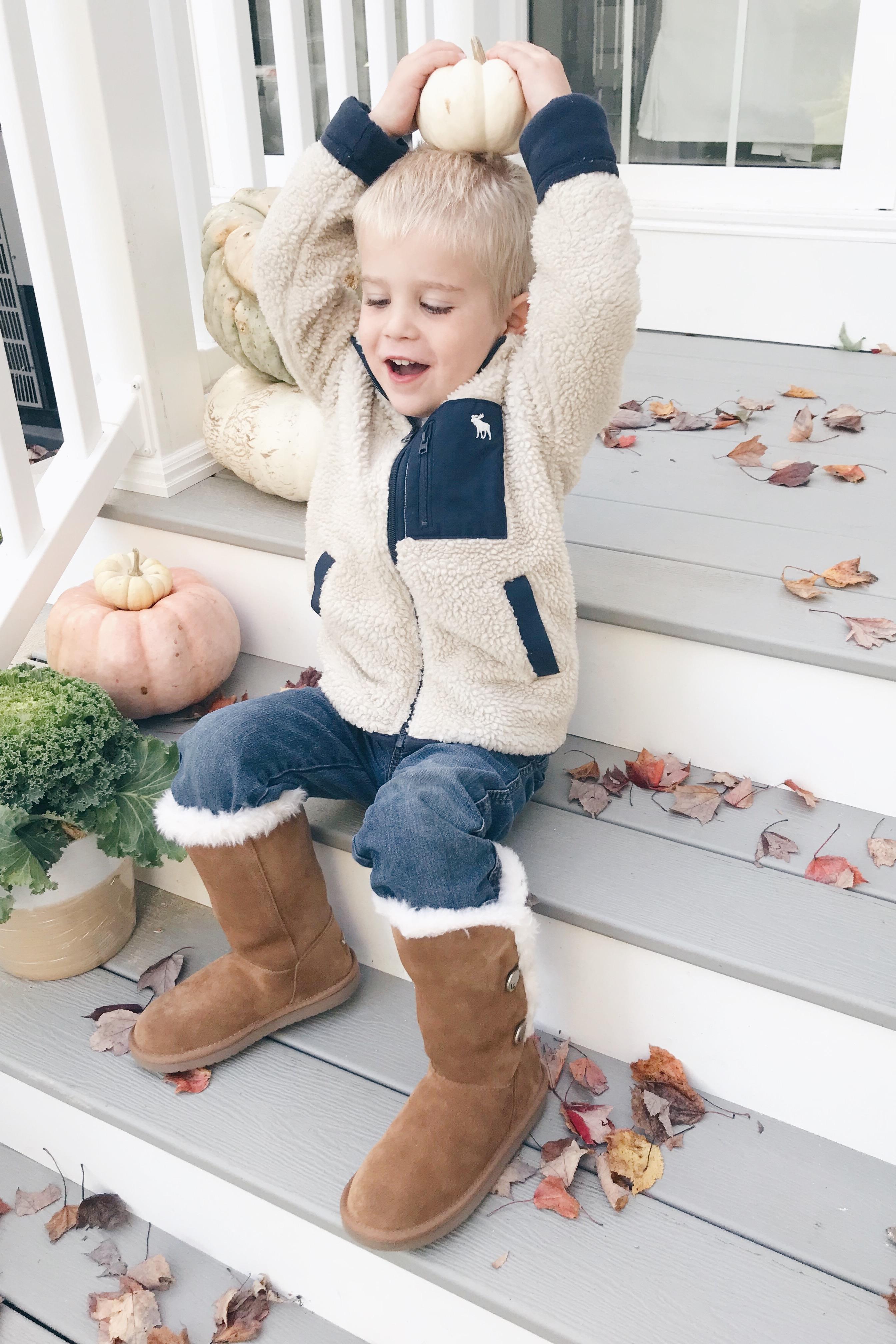 toddler boy on fall porch wearing koolaburra boots
